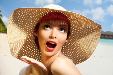 Portrait of surprised woman wearing a straw hat on the beach photo