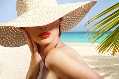 chapeau de paille: Beauty portrait de femme sur la plage portant un chapeau de paille
