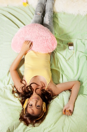 Happy teenage girl in her bed with pink heart shaped pillow Stock Photo - 11753915