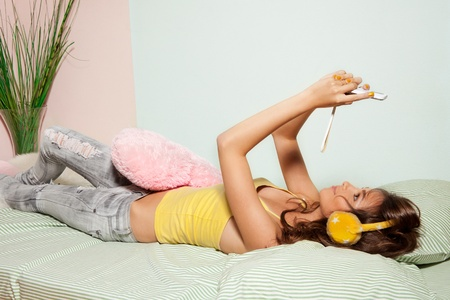 Teenage girl playing games with cell phone laying in bed photo