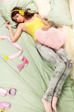 Teenage girl laying in her bed with her clothes and pillows laying around photo