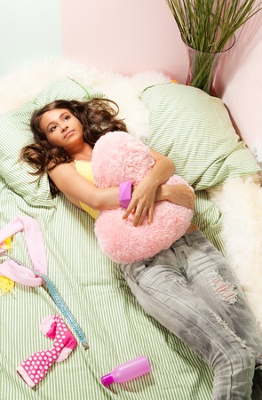 Teenage girl dreaming about her boyfriend laying in bed and hugging the heart shaped pillow photo