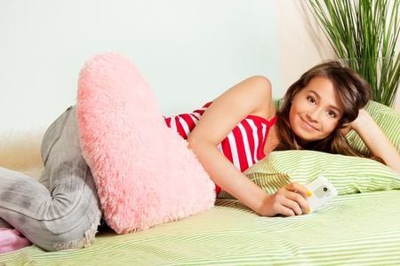 Smiling teenage girl texting from her cell phone laying in bed photo