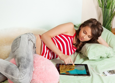 Beautiful teenage girl watching photos from tablet pc laying in bed photo