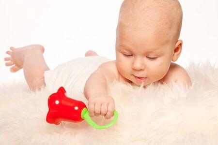 sonaja: Bebé jugando con sonajero por la que se en la cama suave piel