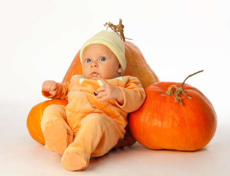 Little baby with pumpkins on white photo