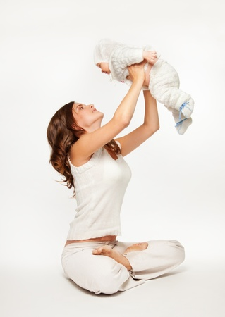 Mother playing with baby by lifting her and sitting in yoga pose