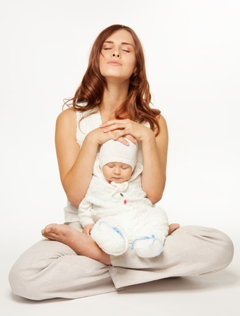 mom holding baby: Mothers meditation - mother meditating sitting in lotus yoga pose with little baby