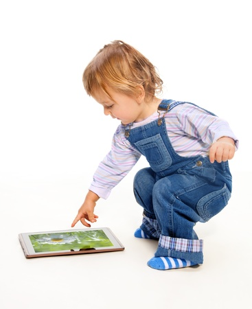 blue jeans kids: Young toddler touching tablet pc (image on the screen from my portfolio) Stock Photo