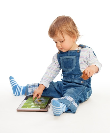 Young kid playing with tablet pc (image on the screen from my portfolio) Stock Photo - 13947927