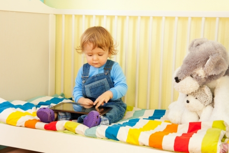 Boy playing with tablet pc sitting in the bed in nursery room photo