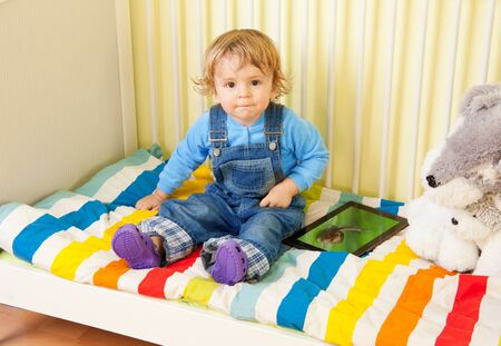 Toddler kid sitting with in the baby bed photo