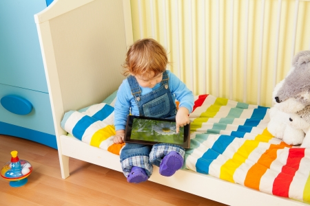 Kid playing with tablet pc in his bedroom photo