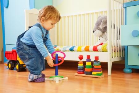 juguetes de madera: Muchacho que juega con el apilamiento de los anillos en el cuarto de ni�os