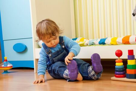 put up: Baby learning putting on sandal sitting in the bedroom