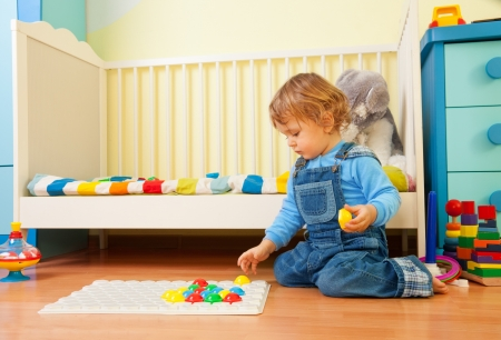 play room: Baby assemble a mosaic in the kids  room Stock Photo