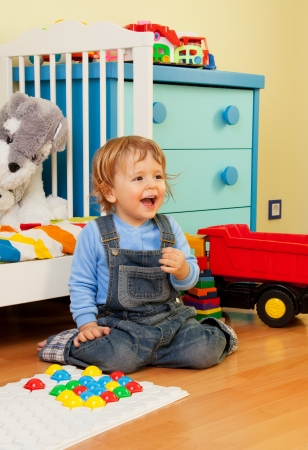 play room: Laughing baby assemble with mosaic sitting in the bedroom Stock Photo