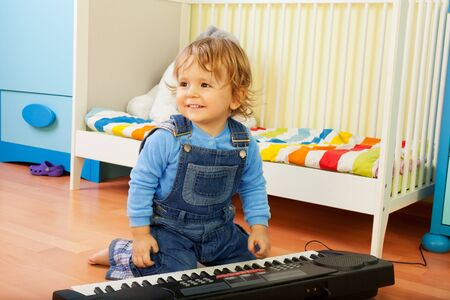 Happy little boy playing a musical instrument - composer photo