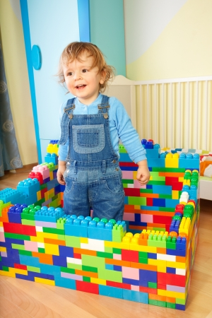 blue jeans kids: Kid playing with toy plastic blocks in the room - building a big house Stock Photo