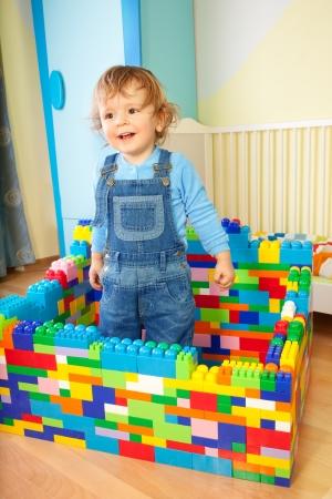 Kid te spelen met speelgoed plastic blokken in de kamer - het bouwen van een groot huis