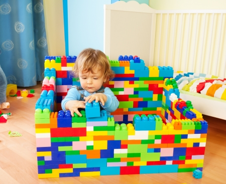 children playing with toys: Smart toddler building a castle of toy plastic blocks Stock Photo