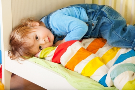 child sad: Tired toddler laying in his bed on a stripped blanket