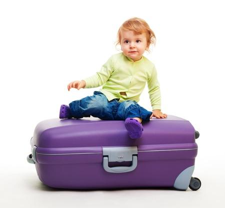Kid sit on the big purple suitcase photo