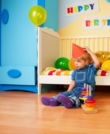 Surprised kid after birthday party sitting on the floor and holding cap photo