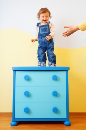Kid jumping from the cabinet on the floor Stock Photo - 13948271