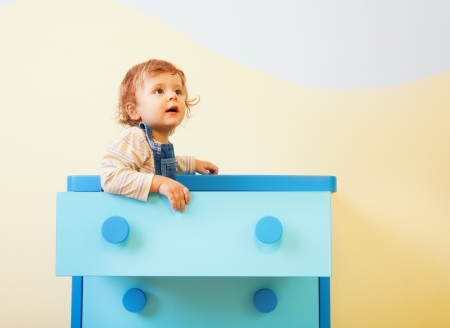 Toddler sitting in the box in kids room Stock Photo
