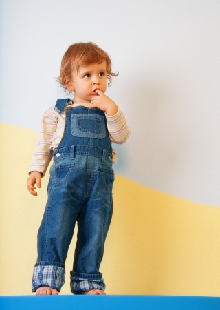 tallboy: Thoughtful kid standing on the furniture Stock Photo