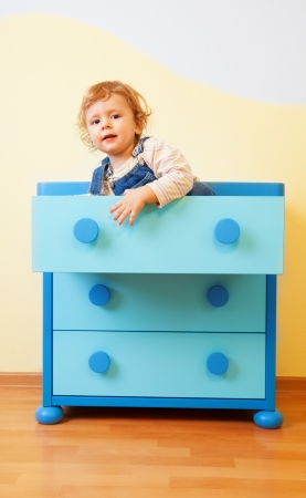 Kid sitting inside blue opened cabinet box photo