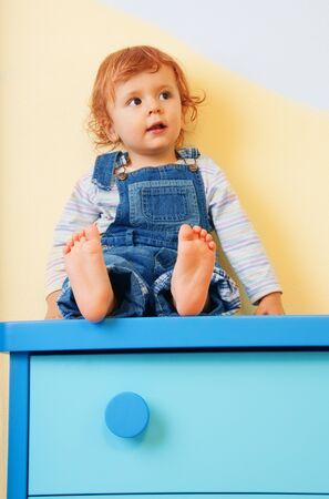 kid sitting on furniture - on the chest of drawers