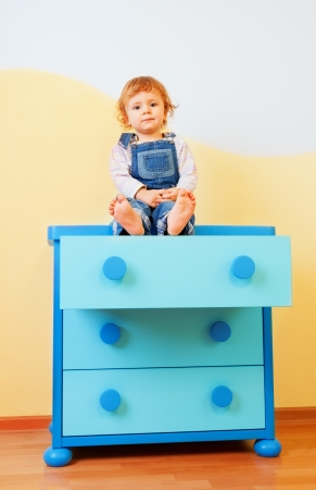 tallboy: Calm happy kid sitting on the cabinet in his room Stock Photo