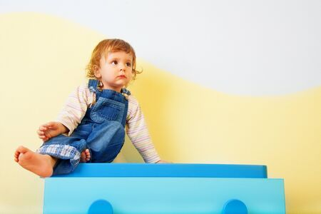 Happy kid sitting on the blue cabinet Stock Photo