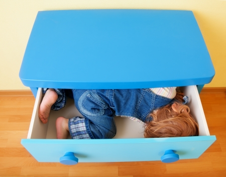 Kid in the open box of cabinet