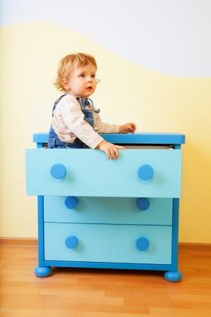 Kid sitting inside opened cabinet box photo