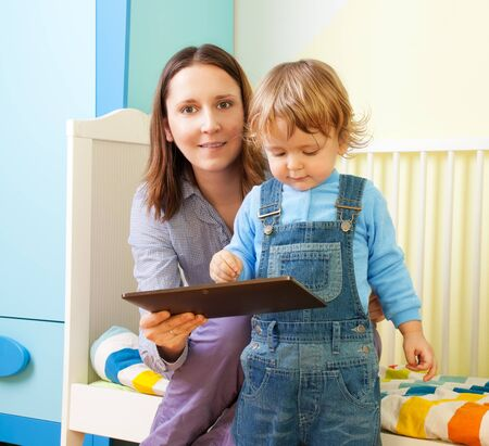 Happy mother with kid and tablet computer in nursery room photo