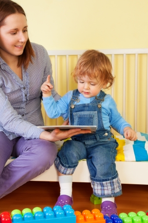 Kid sitting with mother and pointing to the picture  in the book Stock Photo - 13949190