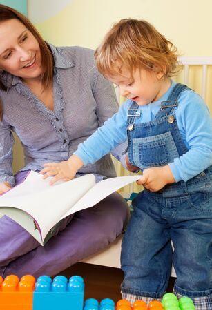 Mother reading a story from book to son toddler sitting in the bed and kid turning pages photo