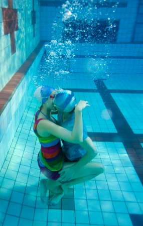 Young couple kissing underwater in the pool photo