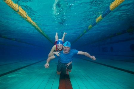 Happy couple underwater swimming together and hugging photo