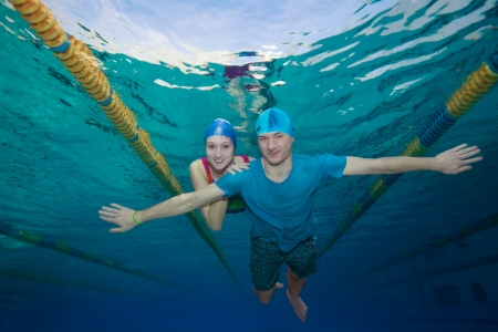 Couple - underwater shoot - swimming together in casual clothes photo