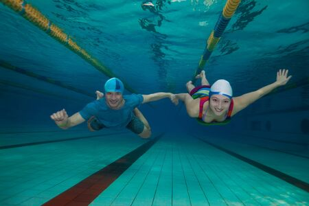 swimming shorts: Underwater fun - couple swimming together holding hands