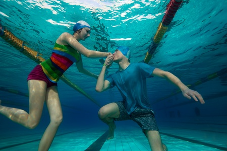 Guy proposing to his fiancée in unusual special pool underwater way photo