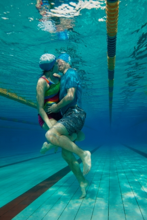 Young couple in casual clothes kissing underwater in the pool Stock Photo