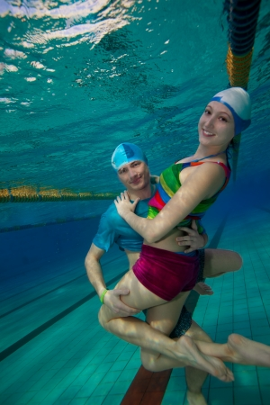 Couple having fun underwater in the pool with guy hug his friend photo