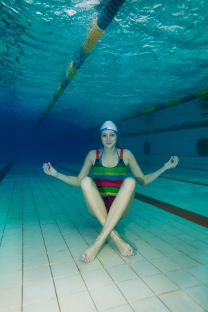 Underwater yoga - girl sitting on the pool floor and meditating Фото со стока