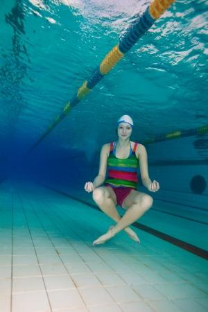 swimming shorts: Girl sitting in yoga pose and meditating underwater Stock Photo