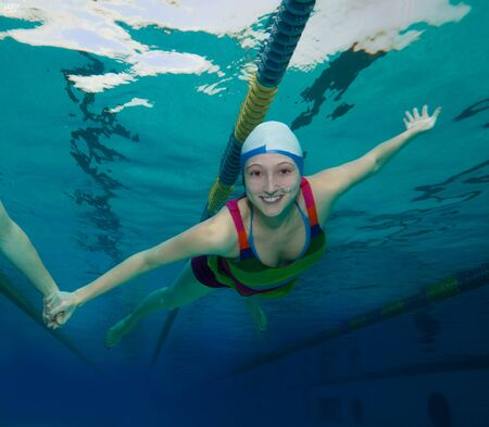 swimming shorts: Girl swimming underwater and smiling holding friend with hand Stock Photo